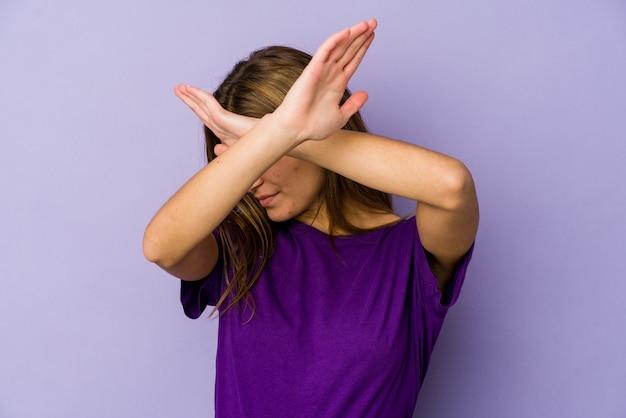 紫色の壁に若い細い白人の女の子のティーンエイジャーは、2つの腕を組んで、概念を否定します。