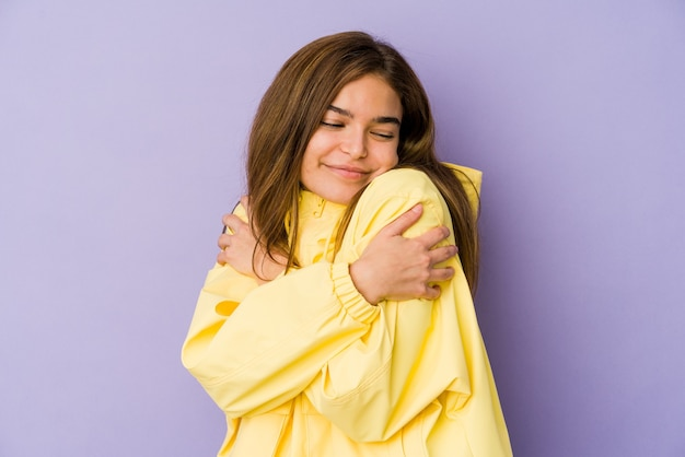 Young skinny caucasian girl teenager on purple background hugs, smiling carefree and happy.