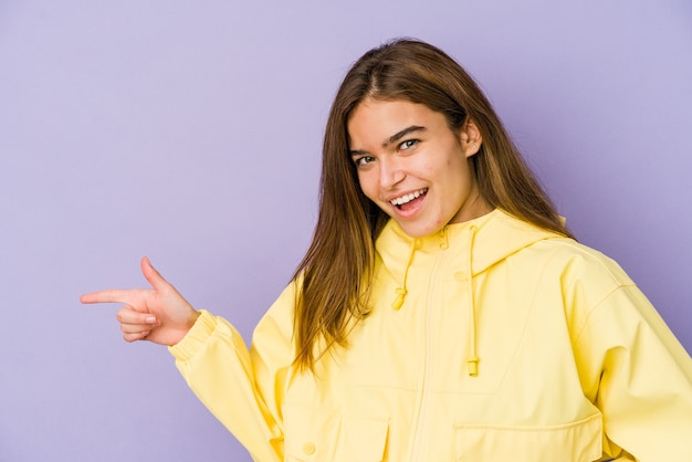 Young skinny caucasian girl teenager on purple wall smiling cheerfully pointing with forefinger away.