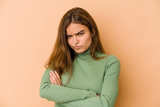 Молодая тощая кавказская девушка-подросток, недовольно хмурясь, держит скрестив руки.