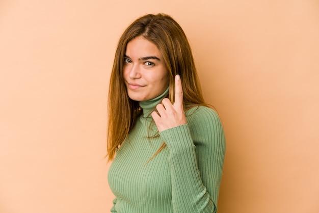 Молодая тощая кавказская девушка-подросток указывает пальцем на вас, как будто приглашая подойти ближе.