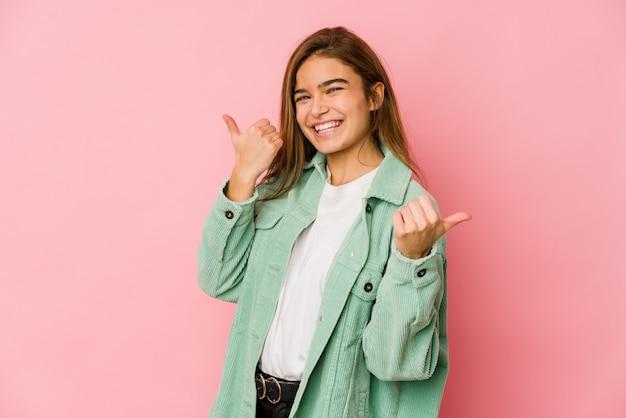 Молодая тощая кавказская девушка-подросток поднимает большие пальцы руки вверх, улыбается и уверенно.