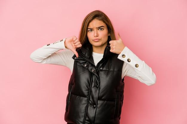 Молодая тощая кавказская девушка-подросток показывает большие пальцы руки вверх и вниз, трудно выбрать концепцию