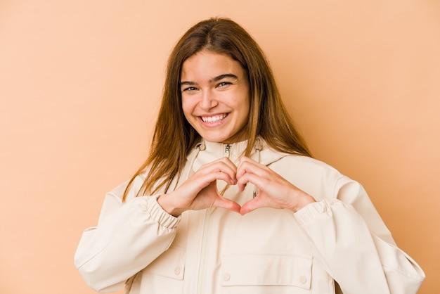 笑顔と手でハートの形を示している若い細い白人のティーンエイジャーの女の子。