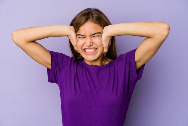 너무 시끄러운 소리를 듣지 않으려 고 손으로 귀를 덮고 젊은 마른 여자 십대 벽