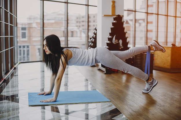 Young and skinny girl in a white shirt and gray leggings engaged in sports at the gym