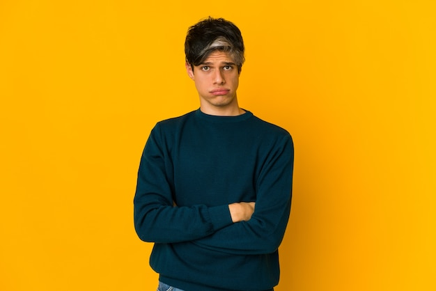 Young skinny hispanic man blows cheeks, has tired expression. facial expression concept.