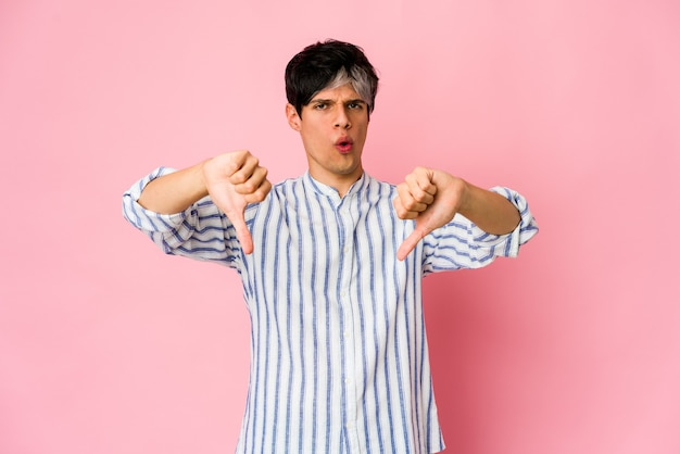 Young skinny hispanic man showing thumb down and expressing dislike.