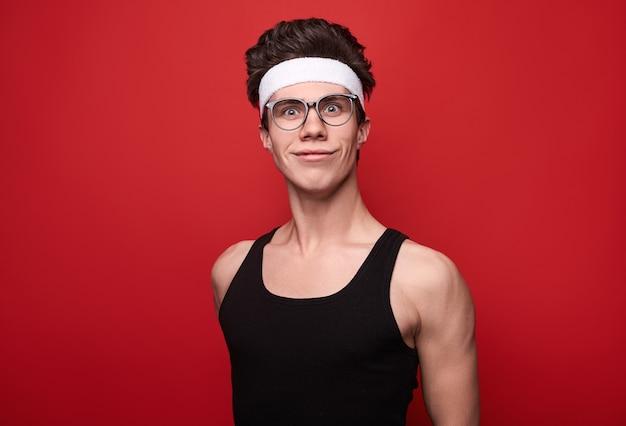 낚시를 좋아하는 옷과 안경을 쓰고 재미있는 얼굴을 만들고 웃고있는 젊은 마른 남성
