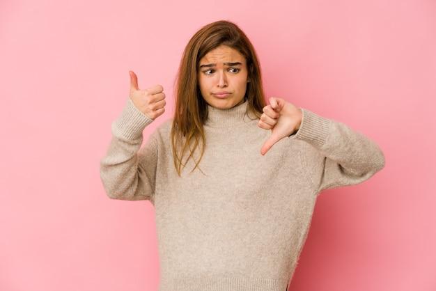Молодая тощая девушка-подросток показывает палец вверх и палец вниз, трудно выбрать концепцию