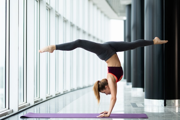 Young skinny woman doing yoga handstand against window in gym