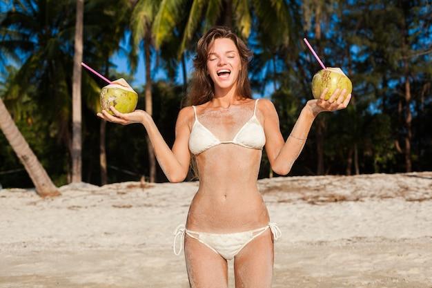 ココナッツを持って、笑顔で、熱帯のビーチで日光浴をしている白いビキニ水着の若い細い女性。