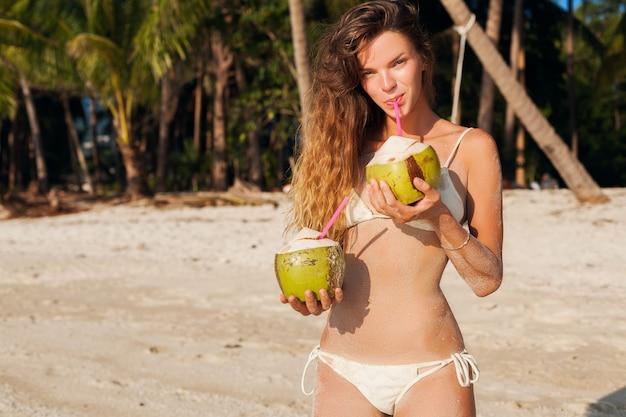 Giovane donna magra in costume da bagno bikini bianco bere noci di cocco, sorridente, prendere il sole sulla spiaggia tropicale.