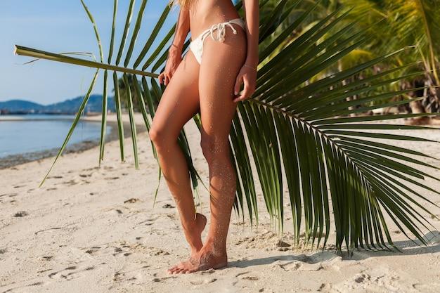 Young skinny woman in white bikini swimwear holding leaf of palm tree sunbathing on tropical beach