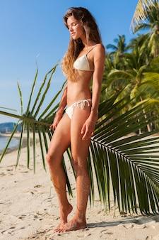 Giovane donna magra in costume da bagno bikini bianco che tiene foglia di palma a prendere il sole sulla spiaggia tropicale.