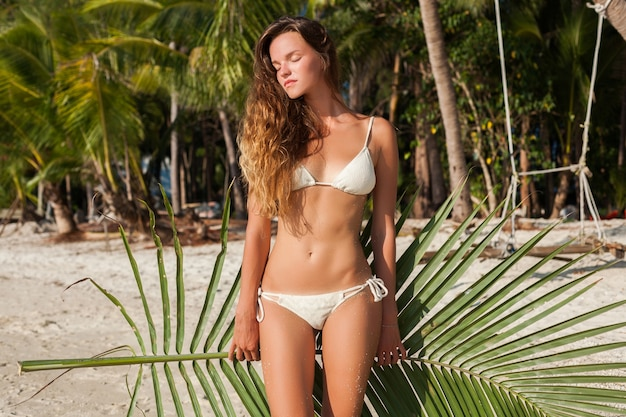 Young skinny woman in white bikini swimwear holding leaf of palm tree sunbathing on tropical beach.