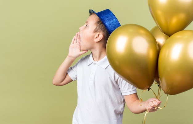 Young slavic boy with blue party hat holding helium balloons and keeping hand close to mouth calling someone looking at side isolated on olive green wall with copy space