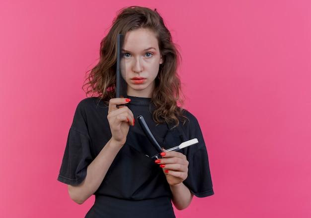 コピースペースでピンクの背景に分離された櫛ストレートかみそりとはさみを保持しているカメラを見て制服を着ている若いスラブ女性理髪師