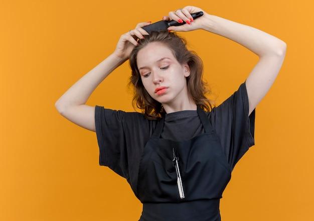 젊은 슬라브 여성 이발사 유니폼을 입고 오렌지 배경에 고립 된 그녀의 머리를 빗질