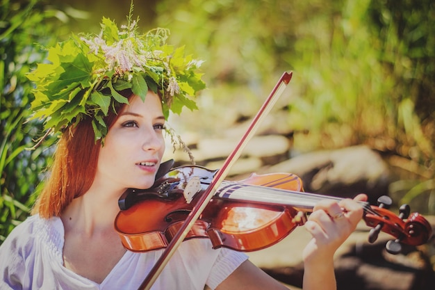 숲에서 바이올린을 연주하는 젊은 슬라브 소녀