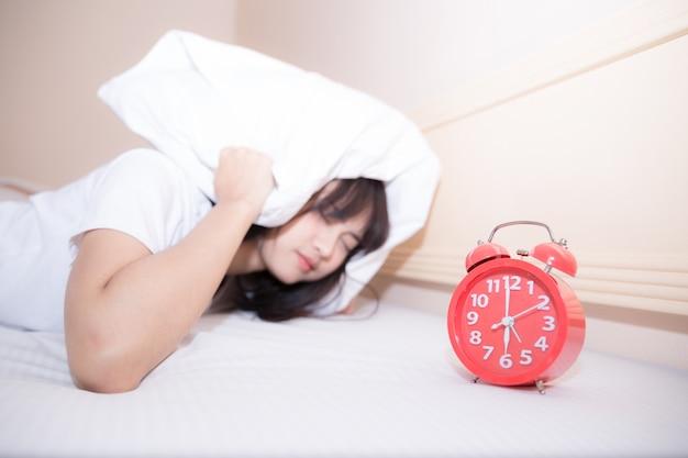 집에서 침실에서 젊은 자 여자와 알람 시계