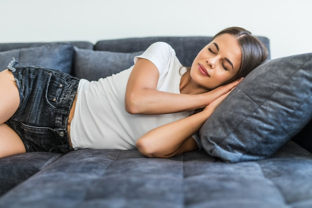 Young sleeping woman is lying on a pillow on a couch