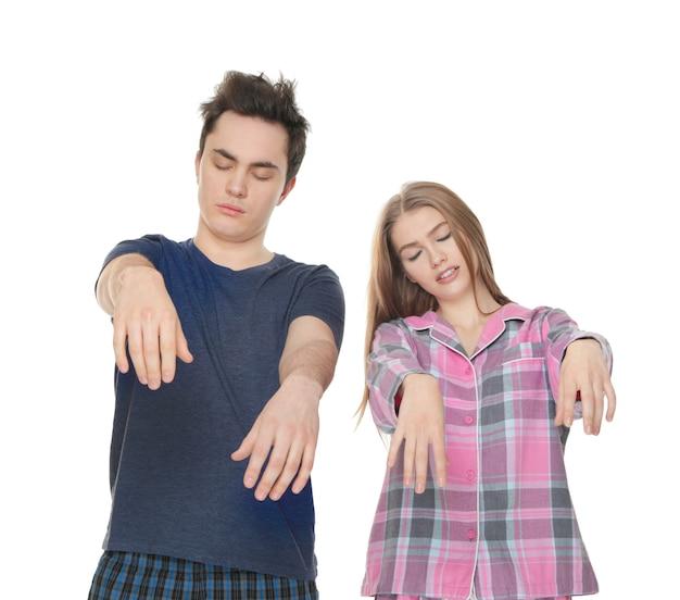 Молодая сонная пара, страдающая сомнамбулизмом на белом фоне