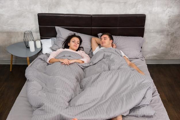 眠そうな若いカップルが目を覚まし、ベッドに横になり、寝室で灰色のロフトスタイルのパジャマを着ています。