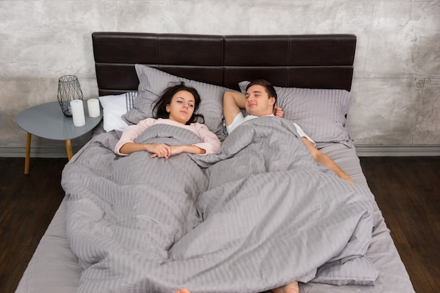 Young sleepy couple wake up and lying in the bed, wearing pajamas in the bedroom in loft style with grey colors