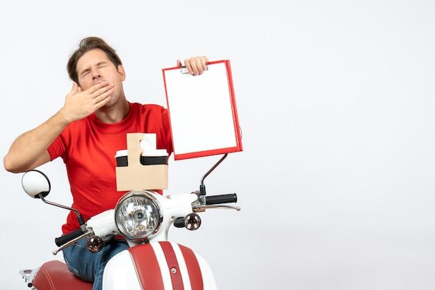 黄色の壁に注文とドキュメントを保持しているスクーターに座っている赤い制服を着た若い眠そうな宅配便の男