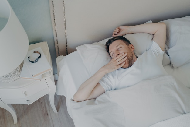 Young sleepy man waking up in morning after night sleep while lying in bed, yawning and covering his mouth with hand and keeping eyes closed. sleeping and bedtime concept