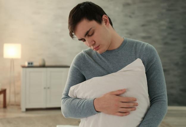 Молодой сонный мужчина с подушкой, страдающий от сомнамбулизма дома