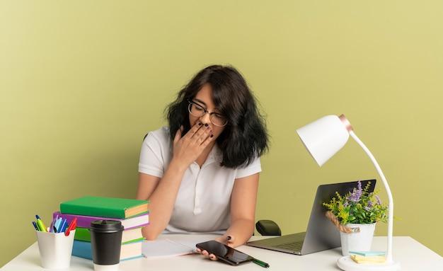 안경을 쓰고 젊은 졸린 예쁜 백인 여학생은 학교 도구와 함께 책상에 앉아 복사 공간이 녹색 공간에 고립 된 전화를 들고 입에 손을 넣습니다