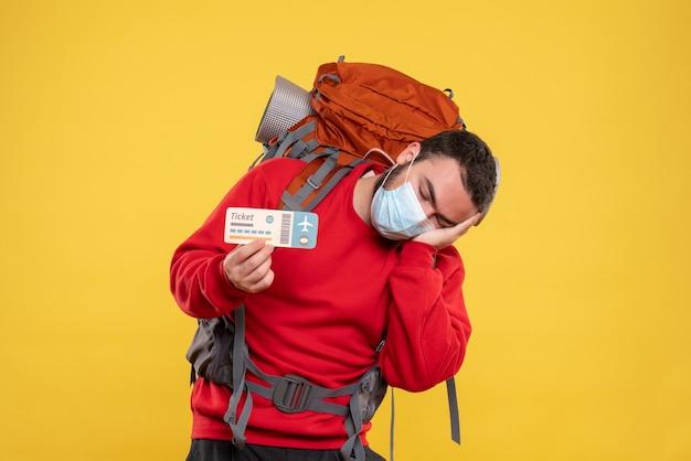 Giovane viaggiatore assonnato che indossa una maschera medica con zaino su giallo
