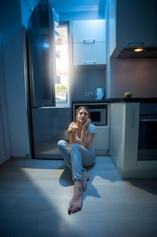 Young sleepy woman sitting on floor at open fridge at late night
