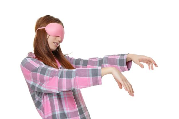 Молодая сонная женщина, страдающая сомнамбулизмом на белом фоне