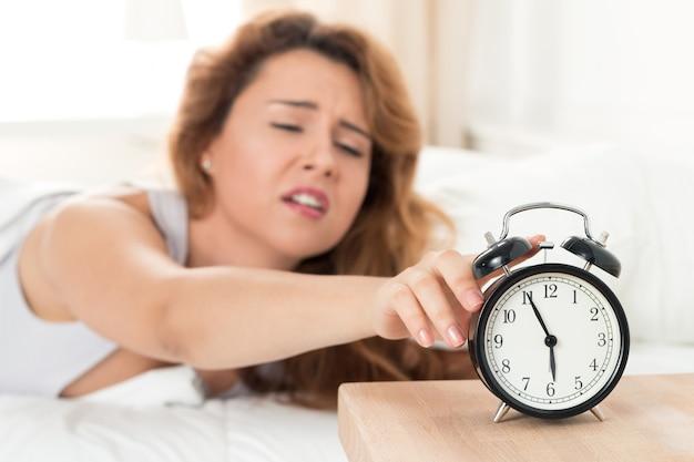 Молодая сонная женщина пытается выключить будильник