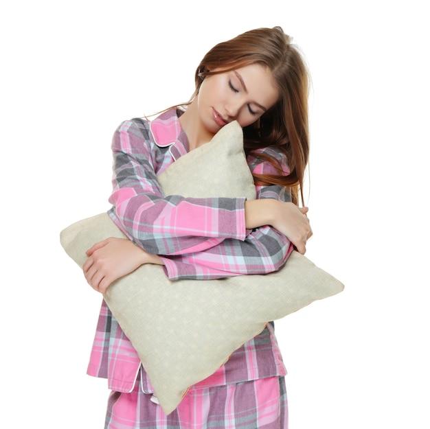 Молодая сонная женщина с подушкой, страдающая сомнамбулизмом на белом фоне