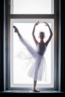 Young slender ballerina in a white tutu dances on pointe shoes in a spacious, bright room with large windows.