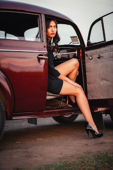 Young slender brunette girl in a black dress sits in a brown retro car and exposed a beautiful leg in high heel shoes