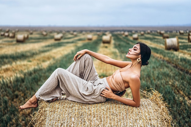 Young slender brunette girl, lying on hay, posing for camera, photo shoot on field, blue sky.