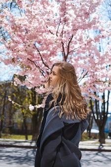 Молодая стройная девушка-модель с длинными волнистыми волосами и, одетая в серое пальто, кеды, крутится на улице. весенние деревья цветут женщина девушка смеется и бежит радоваться