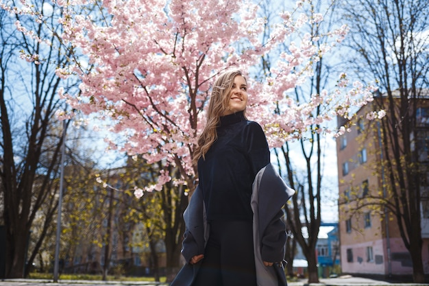 A young slender female model with long wavy hair and, dressed in a gray coat, sneakers, stands on the street near a flowering shrub with beautiful pink flowers in the background and poses.