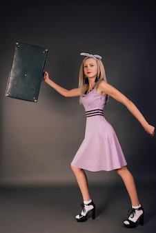 A young slender girl in a pink dress in high heels is hurrying with a suitcase in her hands