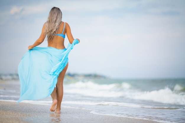 A young slender tanned girl with blonde hair in a gentle bluish swimsuit and a bright light blue shawl, walks along the beach near the edge of the sea water enjoying the warm summer