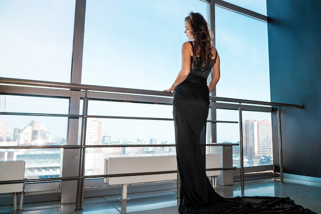 Young slender woman in a black dress opens the panoramic window in the room. sad sad woman at the big window.