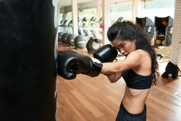 Young slender woman exercising with punching ball in gym