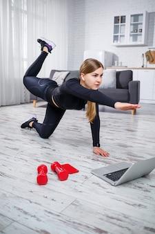 날씬한 젊은 여성이 집에서 스포츠를 하러 들어갑니다. 금발 머리를 한 아름다운 운동가가 집에서 노트북으로 온라인 운동을 보면서 운동을 하고 있습니다. 검역 중 집에서 피트니스.