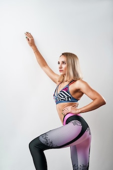 スポーツウェアの若い細身の女性が彼女の筋肉運動の引き締まった体を披露