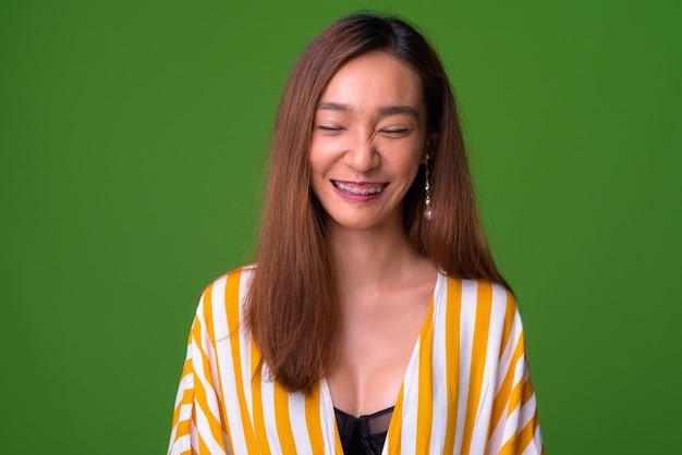 Молодая стройная азиатская женщина на зеленом фоне